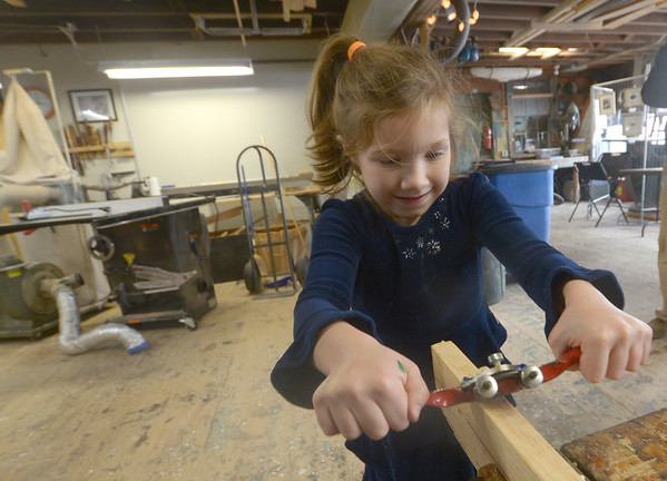JIM VAIKNORAS/ staff photo Kaia Bartosik uses a spokeshave at the annual Holiday Open House at Lowell Boat shop in Amesbury this weekend. Along with wood crafts the event included an art sale, silent auction, chowder, and live music.