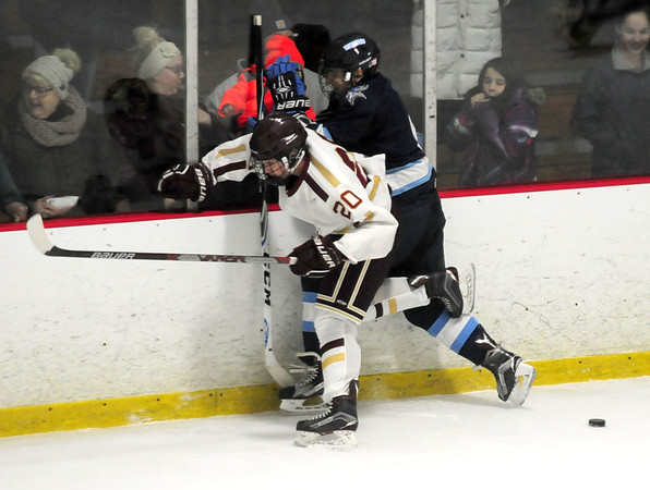 JIM VAIKNORAS/Staff photo Newburyport's Jacob Grossi-Hogg checks triton's Josh D'Arcy during the Viking's 2-1 victory over the Clippers Saturday night at the Graf Rink in Newburyport.