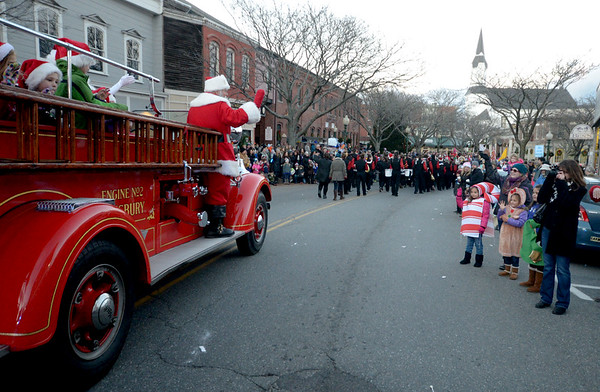 JIM VAIKNORAS/Staff photo Santa waves to the crowds as he makes his way towards Market Square on a vintage  fire truck  in Amesbury Saturday after noon in the city's annual Santa Parade.