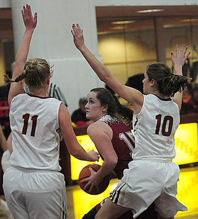 JIM VAIKNORAS/Staff photo Gloucester's Claire Knowlton fight through the defense of Newburyport's #10 Paige Gouldthorpe and #11 Katelyn Hadden during their game at Newburyport High school Wednesday night.