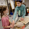 BRYAN EATON/Staff photo. Amesbury Middle School student Molly Tonks, 12, tells Ingrid Allen, 8, about Egyptian mummies and their coffins on Wednesday. The elder students have been learning about ancient Egypt and were presenting their studies to third grade students from Amesbury Elementary and Cashman Schools.