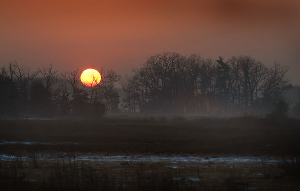 BRYAN EATON/Staff photo. A brilliant sun set over the marshes of Newbury on Route One adjacent to the Parker River. The sun will shine longer after the winter solstice began last Wednesday.