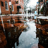 JIM VAIKNORAS/Staff photo Shoppers and building are reflected in puddles on Inn Street caused by Saturday's snow melting in Sunday warm weather.