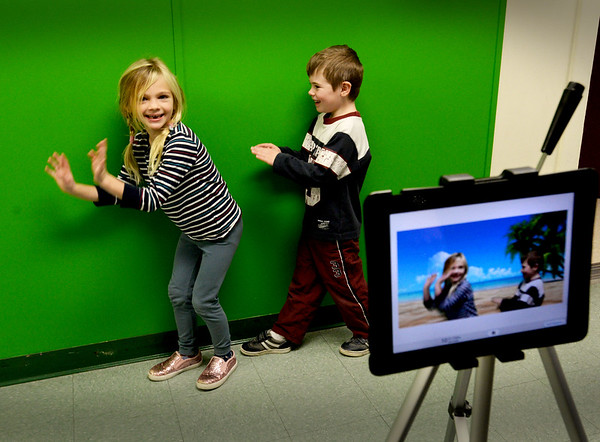 BRYAN EATON/Staff Photo. Students in Bruce McBrien's technology classes are using a new studio with a green screen and with computer magic, students can look like they're in the tropics or anywhere else. Alexa Lindsay, 6, left, and Hayden Lowell, 5, move along the green screen, though on a monitor they appear to be on a beach.