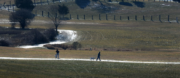 BRYAN EATON/Staff photo. Dog walkers move along a path the wet surface reflecting sunlight at Woodsom Farm in Amesbury on Tuesday morning. The view from the Whitehall Road not far from the South Hampton town line.