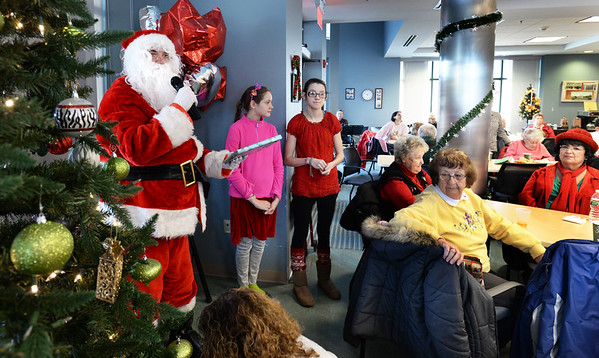 BRYAN EATON/Staff photo. The Amesbury Senior Center hosted their annual Christmas Breakfast with Santa Claus giving out presents and jazz music on Tuesday morning. After breakfast Santa Claus called out numbers to correspond to presents under the tree in the event in which 60 people attended.