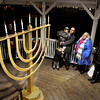 Amesbury: Rachel Barcelona, a Jewish resident of Amesbury, second from right, arranged for a Menorah to be placed for the first time in Amesbury's downtown Gazebo. Rabbi Avi Poupko, center, led the public in the lighting of the Amesbury Menorah last night and here sing after the lighting. Bryan Eaton/Staff Photo