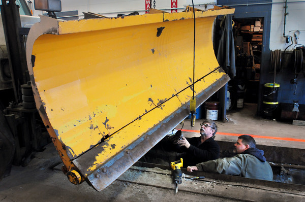 Salisbury: Salisbury DPW employees Ray Cote, left, and Kirk Salvatore repair the underpinning of one of the town's plows as they get equipment checked out for the impending storm. Over six inches of snow is in the forecast for tomorrow into Friday. Bryan Eaton/Staff Photo
