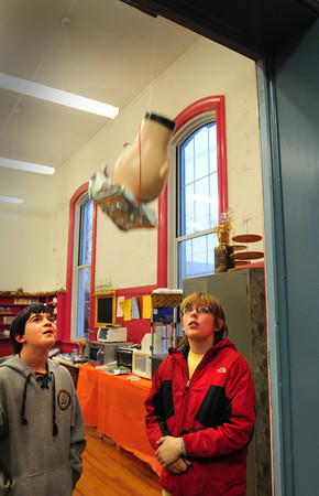 Newburyport: Zack Naughton, 11, left, and Luke Young, 12, watch as a mannequin head they fitted with a helmet they made drops to the floor at the Kelley School Youth Center. The center was piloting a Museum of Science curriculum for afterschool programs and the students were testing to see how well each helmet stood up on impact. Bryan Eaton/Staff Photo
