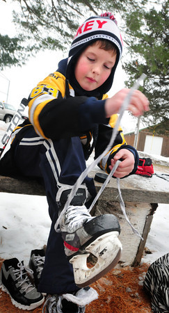 Amesbury: Ian Pelletier laces up ready for practice his ice skating skills on the rink at Amesbury Town Park on Thursday. He was there with his father, Jeff, who coaches Amesbury Youth Hockey, of which the nine year-old is a player. Bryan Eaton/Staff Photo