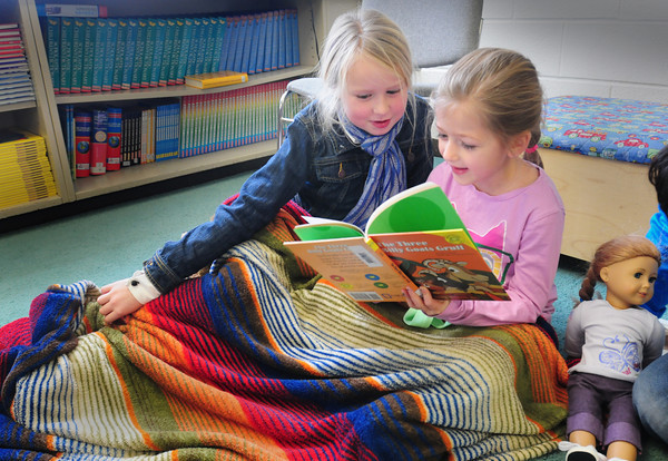 """Amesbury: Tuesday was a good day to get warm under a blanket and read some books as Caitlyn Creps, left, and Olivia Houston, both 7, did at Amesbury Elementary School as temperatures started at zero in the morning with more snow on the way. Librarian Lori Byman read the children """"Kirsten's Surprise: A Christmas Story"""" then the second-graders read books of their own as they brought pillows, blankets and friends or dolls. Bryan Eaton/Staff Photo"""
