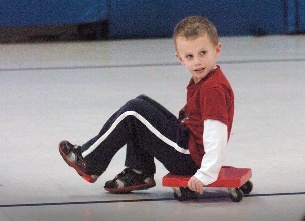 """Amesbury: John Taber, 5, pulls him self along escaping others in Margaret Welch's phys ed class at Amesbury Elementary School on Monday. He and his classmates were playing a game of """"scooter tag."""" Bryan Eaton/Staff Photo"""