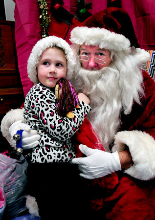Amesbury: Liliana Healey, 3, gets a hug from Santa Claus after he gave her a Christmas stocking filled with goodies Wednesday night at Our Neighbor's Table in Amesbury. Bryan Eaton/Staff Photo