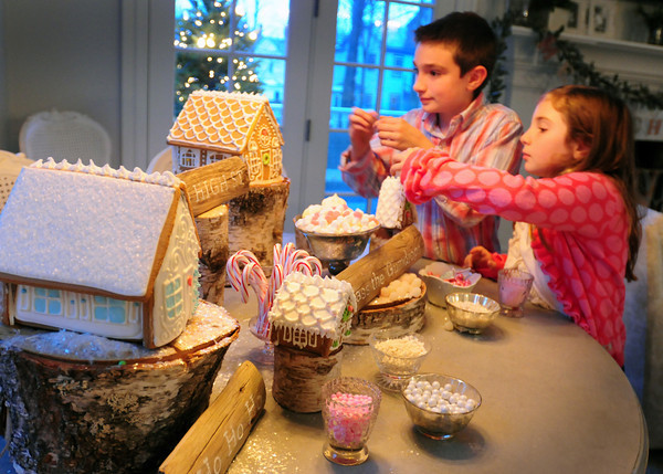 Newburyport: Todd Santos, 6, and his sister Ella, 6, contributed to the effort by putting finishing touches on gingerbread houses. Bryan Eaton/Staff Photo