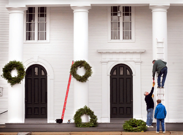 Amesbury: Members of the Main Street Congregational Church in Amesbury decorated the front of the building with wreaths. Ted Morse hands Roger Jones some wire, while Donna Jones keeps the ladder steady. Bryan Eaton/Staff Photo