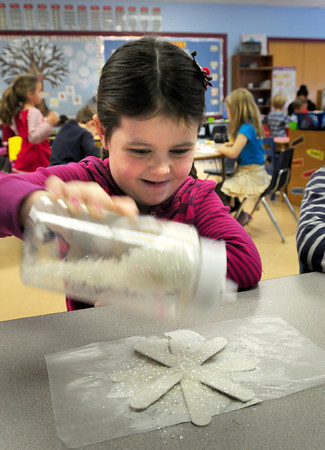 Rowley: Delaney Quinn, 5, shakes glitter onto tongue depresses glued together to create a giant snowflake on Thursday. The kindergartner was in Lisa Manganello's class at the Pine Grove School in Rowley. Bryan Eaton/Staff Photo