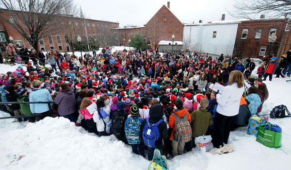 Amesbury: Amesbury Elementery students under the direction of music teacher Alicia Harlov , sing holiday songs in the Upper Millyard in Amesbury Friday afternoon. Jim Vaiknoras/staff photo