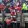 Newburyport: Santa gets a hand from a member of the Coast Guard as he is helped up from a Coast Guard boat onto the boardwalk before the annual Newburyport Christmas Tree Lighting Sunday. jim Vaiknoras