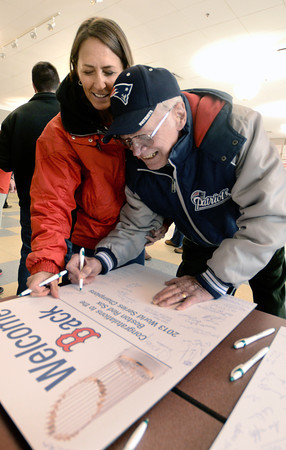 Amesbury: Bonnie Bebsch and her dad Donald, who once tried out for the Red Sox,sign a card  congradulating the Sox after they visited with the Red Sox 2013 World Series trophy at Amesbury high school Friday. Jim Vaiknoras/staff photo