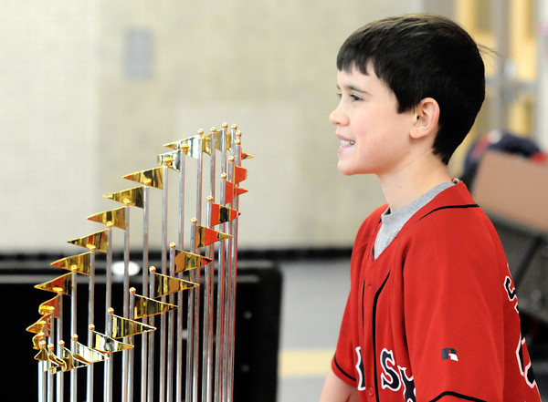Amesbury: Ryan Archer, 11, of Newburyport poses with the Red Sox 2013 World Series trophy at Amesbury high school Friday, Jim Vaiknoras/staff photo