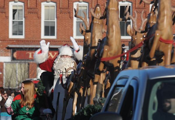 JIM VAIKNORAS/Staff photo Santa leads his team of reindeer down Main Street in Merrimac at Merrimac Santa parade Sunday.