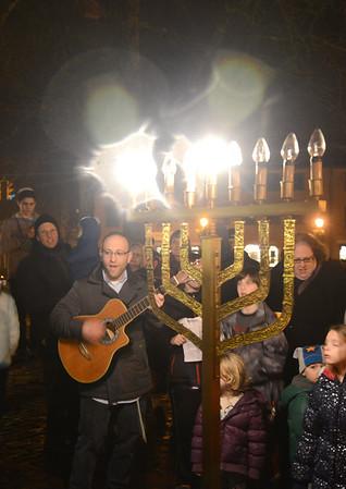 JIM VAIKNORAS/Staff photo Rabbi Avi Poupko leads a large gathering in Market Square in Hanukkak song at the annual lighting Menorah.