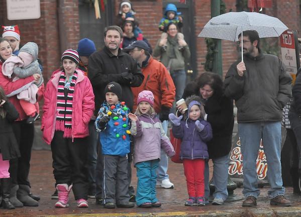 JIM VAIKNORAS/Staff photo Kids brave the rain at as the Amesbury Santa parade makes it's way towards Market Square Saturday.
