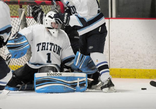 BRYAN EATON/ Staff Photo. Triton goalie Nolan Smith deflects a Medford shot on net last night at the Graf Rink.