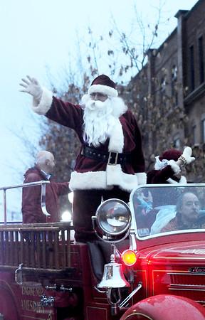 JIM VAIKNORAS/Staff photo Santa makes his way down Main Street in the rain during the Amesbury Santa parade Sunday night.