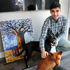 Newburyport: Newburyport dentist Sam Merabi with dogs Bravo, front, and Razi in front of a painting of a baobob tree in Malawi, Africa. Bryan Eaton/Staff Photo