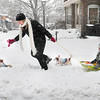 Newburyport: Ginny DeRosa of Amesbury has her hands full as she walks her dogs, Dolly and Nickle, and tows her sons, Nicolas, 6, right, and Michael, 4, on Pleasant Street in Newburyport at the top of Inn Street during yesterday's storm. The snow forecast for Sunday night has been downgraded at this point by meteorologists. Bryan Eaton/Staff Photo