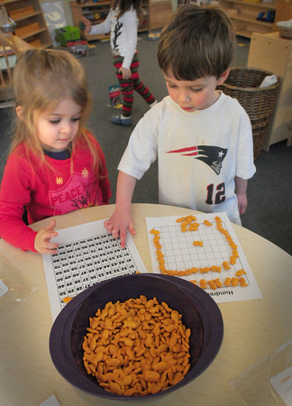 Newburyport: Carey Cavallaro, left, and Eamon Brown, both 3, count out 100 goldfish snacks at the Newburyport Montessori School on Monday morning. It was the 100th day of school which also coincided with their Pajama Day. Bryan Eaton/Staff Photo