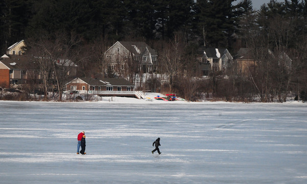 Amesbury: An adult with two children crossed Lake Gardner from Whitehall Road to the bast of Powow Hill in Amesbury on Thursday morning. The ice should be around for a bit as temperatures for the next week only get to freezing and below with more snow on the way Sunday night. Bryan Eaton/Staff Photo