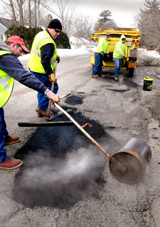 Newburyport: This crew from the Newburyport Department of Public Services was driving through the city yesterday repairing potholes. Here they fill in a large one on Ferry Road near Noble Street. Bryan Eaton/Staff Photo