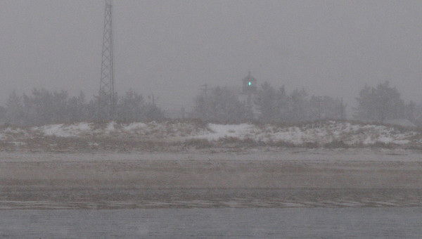 Newburyport: Plum Island Light can be seen shining through a snow squall in a photo taken from Salisbury Beach State Reservation. Bryan Eaton/Staff Photo