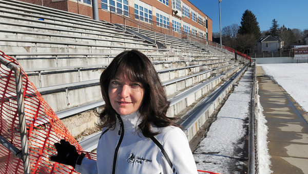 Newburyport: Lise Reid, parks administrator for Newburyport, in front of the dilapitated north bleachers at World War Memorial Stadium. Bryan Eaton/Staff Photo