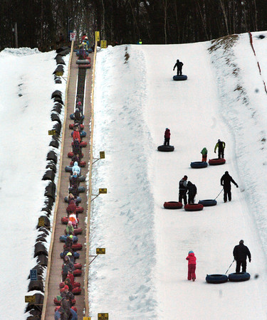 Amesbury: Some people chose to walk their tubes up the hill at Amesbury Sports Park on Tuesday afternoon. Despite the warm temperatures this past weekend, there was plenty of snow for the school vacationers from New Hampshire. Bryan Eaton/Staff Photo