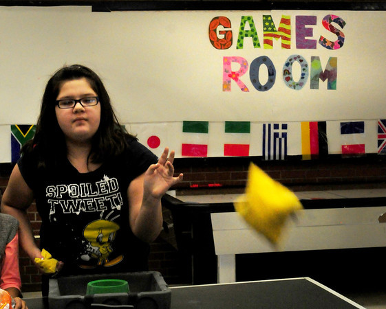Salisbury: Abbrielle Carrera, 12, tosses a bean bag as she and friend  Kailey Tidd, 10, play a game of Bean Bag Toss. The two were in the games room at the Boys and Girls Club on Tuesday afternoon. Bryan Eaton/Staff Photo
