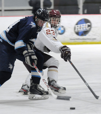Newburyport: Newburyport's Matthew Kelleher reaches for the puck with triton's Kyle Hillick during the Newburyport Bank 19 Annual Hockey Classic. Amesbury won the game in a shootout. Jim Vaiknoras/staff photo