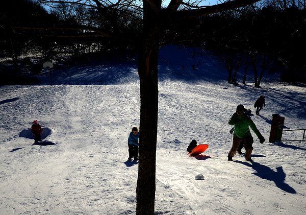Newburyport; Sledders cast long shadows as they enjoy the cold sunshine Monday on Marches Hill in Newburyport. Jim Vaiknoras/staff photo