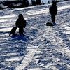 Amesbury: Two sledders make their way up the hill at Woodsom Farm in Saturday bright sunshine. Jim Vaiknoras/staff photo