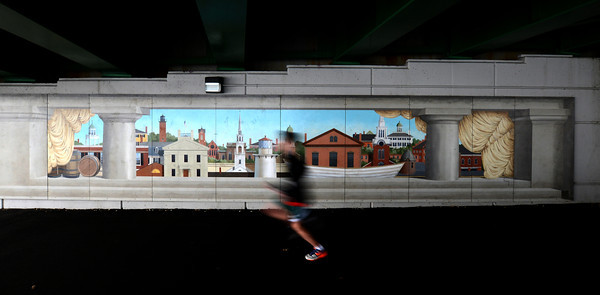 Newburyport: A runner in the Frigid Fiver Road Race sprints by the mural along the Rail Trail under the Gillis Bridge in Newburyport Sunday afternoon. Jim Vaiknoras/staff photo