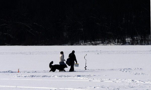 Newburyport: Ice fishermen, and dog, move from trap to trap Sunday afternoon on the Artichoke Reservoir. Jim Vaiknoras/staff photo