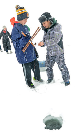 Merrimac: Keegan Comeau and Aidan Smith set their lines for ice fishing  at the Lake Attitach Winterfest Saturday in Merrimac. Jim Vaiknoras/staff photo