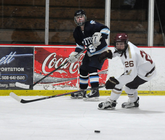 Newburyport: Triton's Joe Schickling clears the puck past Newburyport's Tyler Therrien during the Newburyport Bank 19 Annual Hockey Classic. Amesbury won the game in a shootout. Jim Vaiknoras/staff photo