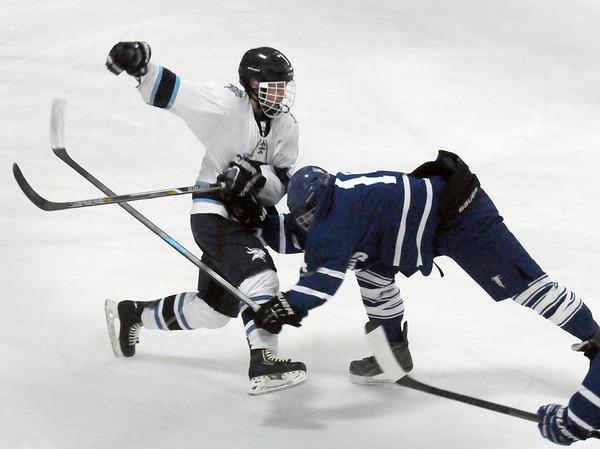 BRYAN EATON/Staff Photo. Danvers player Sean Lundergan goes down as Triton's Jake Daniels sent the puck down ice.
