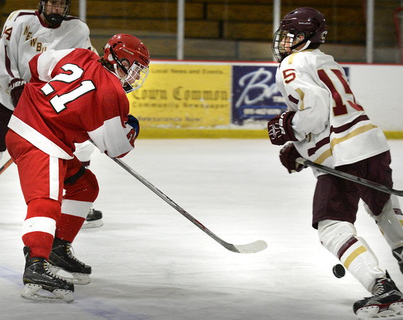 BRYAN EATON/Staff Photo. Amesbury's Patrick Birmingham slides the puck past Newburyport's Dylan Rogers.