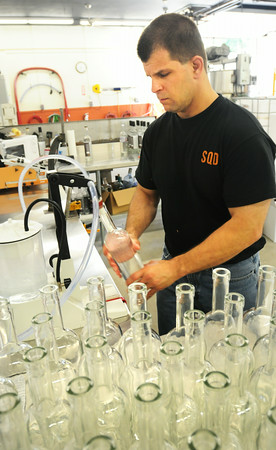 BRYAN EATON/ Staff Photo. Kevin Kurland fills corn mash moonshine and vodka bottles by hand.