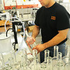 BRYAN EATON/ Staff Photo. Kevin Kurland fills corn mash moonshine and vodka bottles by hand.