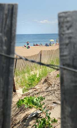 """BRYAN EATON/ Staff Photo. Sunbathers are framed by snow fencing at Salisbury Beach on Tuesday which really was a true """"beach day."""""""